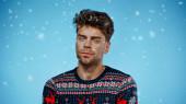 Mladý muž ve svetru při pohledu na kameru pod padajícím sněhem na modrém pozadí