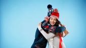 Mosolygós nő kalap és pulóver ölelés barátja ajándék doboz kék háttér