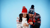 Smiling couple in warm clothes using smartphone on blue background