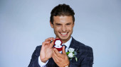 cheerful bridegroom showing jewelry box with wedding ring isolated on blue