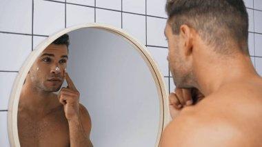 Young man applying face cream near mirror in bathroom stock vector