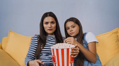 Mother and daughter watching movie near bucket with popcorn stock vector