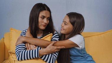 Smiling girl hugging upset mother in living room stock vector