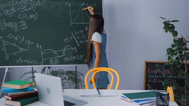 Back view of girl writing mathematical graph on chalkboard stock vector