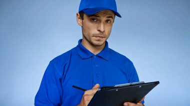 Serious delivery man writing order on clipboard isolated on blue stock vector