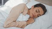 fiatal nő csukott szemmel alszik az ágyban