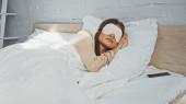 žena v masce oka spí v blízkosti smartphonu s prázdnou obrazovkou