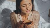 vysoký úhel pohledu na šťastnou ženu drží šálek čaje a dívá se jinam