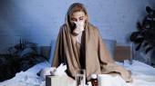 Kranke niest in Serviette, während sie neben Medikamenten im Bett sitzt