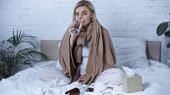 beteg nő ivóvíz, miközben ül az ágyban közelében gyógyszerek