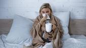 Kranke Frau niest in Papierserviette, während sie im Schlafzimmer mit Tasse Tee fernsieht