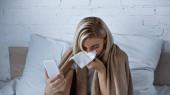 Kranke Frau niest in Papierserviette und hält Smartphone im Schlafzimmer
