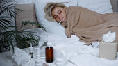 sick woman measuring temperature in bed near napkins and medications on blurred foreground
