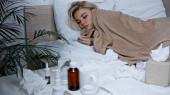 Kranke Frau hält Thermometer im Bett neben Medikamenten auf verschwommenem Vordergrund