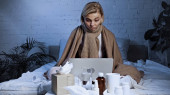 beteg szabadúszó dolgozik laptop alatt takaró a hálószobában