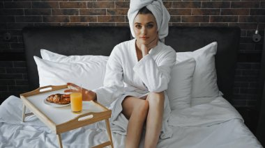 Woman in white towel and bathrobe looking at camera near tray with breakfast on bed stock vector
