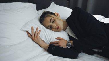 Businesswoman in formal wear sleeping on bed in hotel room stock vector