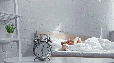 Retro alarm clock near sleepy woman lying on bed in morning stock vector