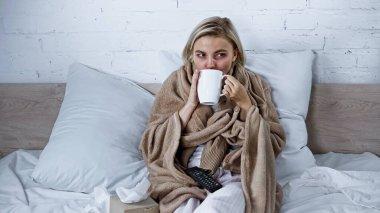 Diseased woman drinking warm beverage while watching tv in bedroom stock vector