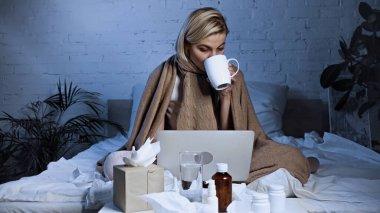 Sick freelancer drinking warm tea near laptop and medications in bedroom stock vector