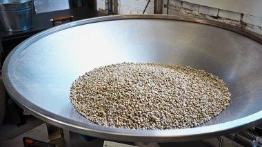 Raw coffee beans in modern roasting machine stock vector