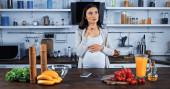 Schwangere steht neben Smartphone und frischen Zutaten in Küche