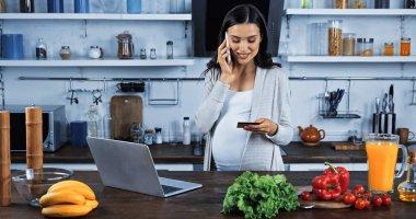 Mutfakta yemek yerken elinde kredi kartıyla akıllı telefondan konuşan hamile bir kadın.