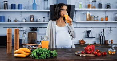 Pregnant woman drinking orange juice near organic food in kitchen stock vector