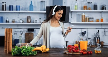 Smiling pregnant woman in headphones using smartphone near fresh food in kitchen