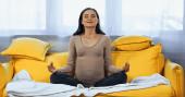 Lächelnde Schwangere meditiert mit geschlossenen Augen auf Couch
