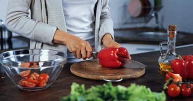 Cropped view of woman cutting bell pepper on cutting board near oil and vegetables on blurred foreground stock vector