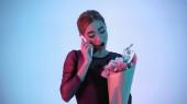 balerína drží květiny, zatímco mluví na smartphone na modré