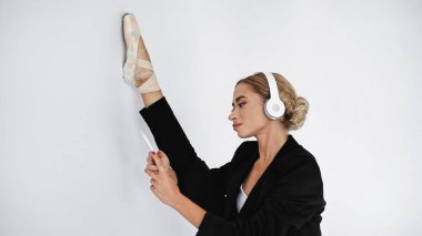 flexible ballerina in suit and pointe shoes listening music while holding smartphone and stretching on white