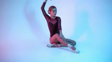young ballerina in pointe shoes dancing on blue background