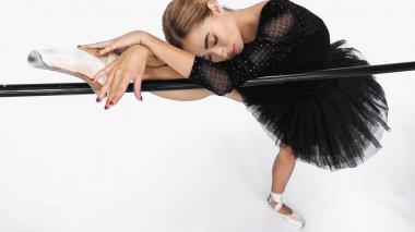 Elegant ballerina in tutu skirt stretching near barre on white background stock vector