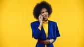 Lächelnde Afroamerikanerin in blauer Jacke unterhält sich auf Smartphone isoliert auf gelb