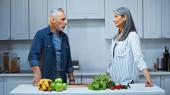 šedovlasý multikulturní pár při pohledu na sebe, zatímco stojí v blízkosti ovoce a zeleniny v kuchyni