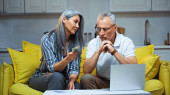 grey haired asian woman holding dollars near laptop and serious husband