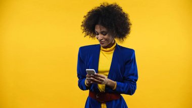 Smiling african american woman in blue jacket using smartphone isolated on yellow stock vector