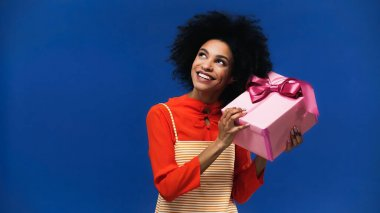 Happy african american woman holding gift box isolated on blue stock vector