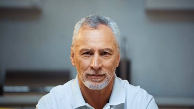 Grey haired, bearded elderly man smiling at camera at home stock vector