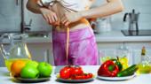 oříznutý pohled ženy měřící pas v blízkosti zeleniny a ovoce na rozmazaném popředí