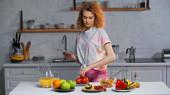 kudrnatá žena drží zápisník a váží rajčata v blízkosti zeleniny a pomerančové šťávy na stole