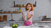 kudrnatá mladá žena mluví na smartphone a drží jablko v blízkosti kukuřičné vločky v kontejneru na stole