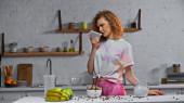göndör nő felvétel hangüzenet közelében kukorica pelyhek és gyümölcsök konyhaasztalon