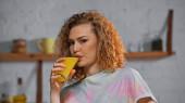 göndör nő nézi kamera közben ivás narancslé a konyhában