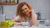 kudrnatá žena se usmívá blízko hromady kukuřičných vloček v misce