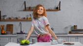 veselá a kudrnatá žena stojící u kuchyňského stolu s jablky a kukuřičnými vločkami