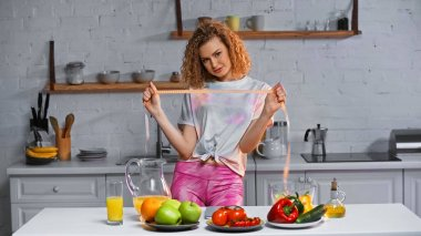 Cheerful woman holding measuring tape near veggies on kitchen table stock vector