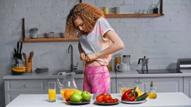 Curly woman measuring waist with measuring tape near veggies on kitchen table stock vector